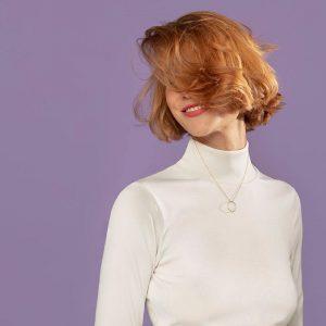 uśmiechnięta kobieta z zasłoniętą twarzą przez włosy