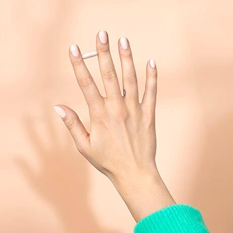 kobieca dłoń trzymająca kapsułkę wimin pomiędzy palcami