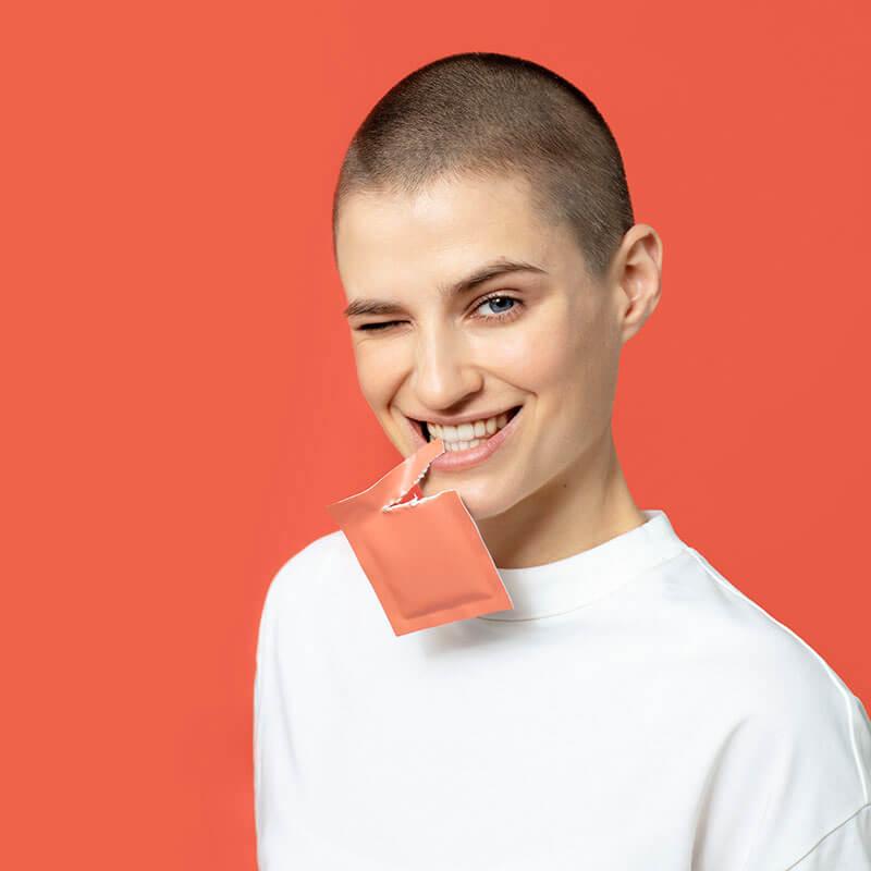 uśmiechnięta dziewczyna trzymająca w zębach saszetkę wimin pms